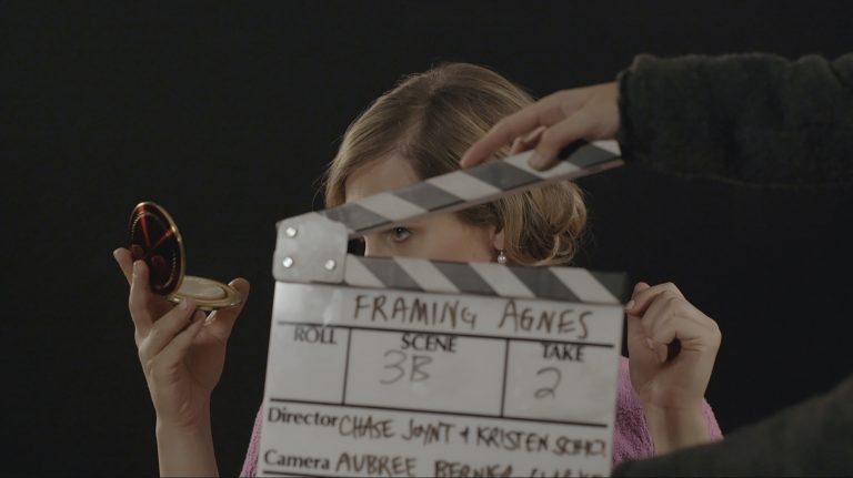 movie slate in front of transfem checking her make-up