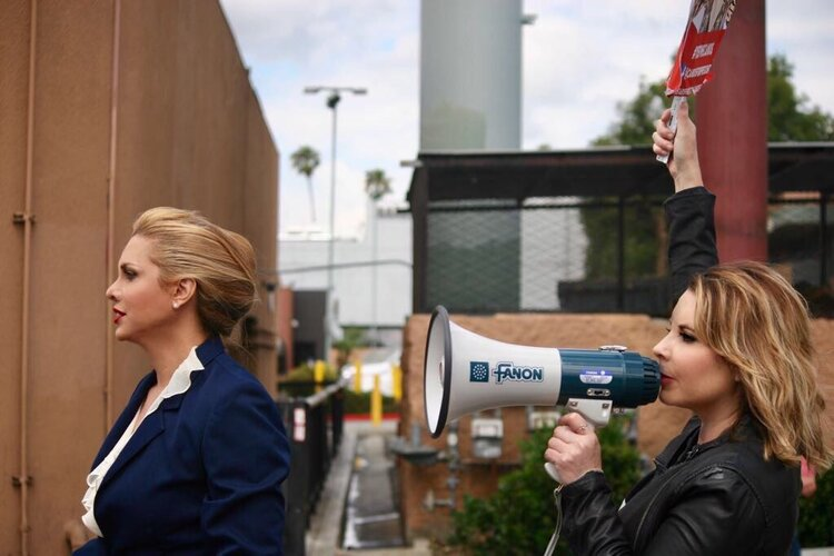 two blonde women, one with bullhorn
