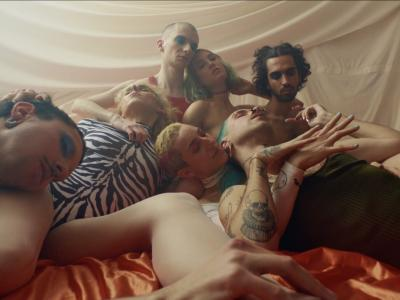 A diverse group of trans people lie together on a bed of orange satin